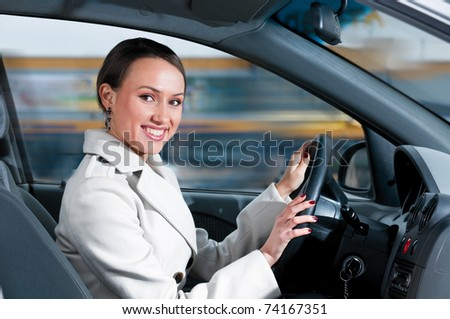 happy business woman in a car is looking at camera - stock photo