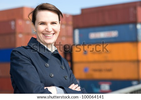 Happy business woman in front of cargo container terminal - stock photo