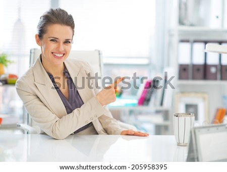 Happy business woman in office pointing on copy space - stock photo