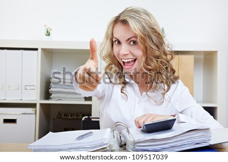 Happy business woman in office with files holding thumbs up - stock photo