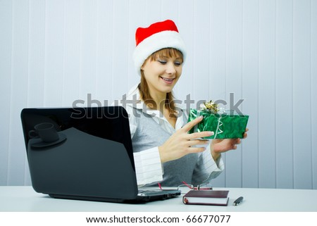 happy business woman in Santa hat with a gift at the office - stock photo