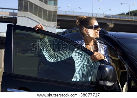 happy business woman in sunglasses near the car against city bridge