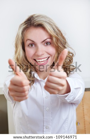 Happy business woman in the office holding both thumbs up - stock photo