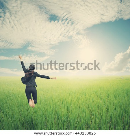 Happy business woman jumping in green rice field and clouds sky.Vintage tone. - stock photo