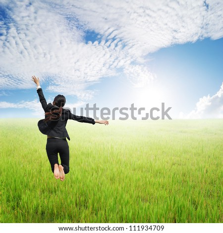 Happy Business woman jumping to clouds sky in grassland - stock photo
