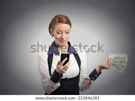 Happy business woman looking at smart phone throwing away cash dollar bills isolated grey wall background. Face expressions. Making spending money financial reward compensation concept  - stock photo