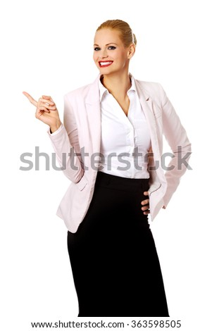 Happy business woman pointing at copyspace or something - stock photo