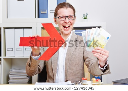 Happy business woman pointing with arrow to Euro money bills - stock photo