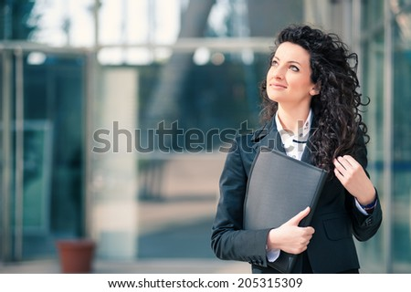Happy business woman portrait outdoors with modern building as background.
