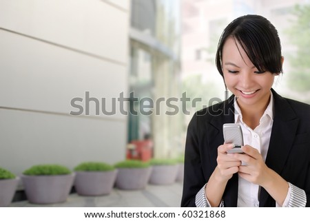 Happy business woman reading SMS and smiling outside of office building. - stock photo
