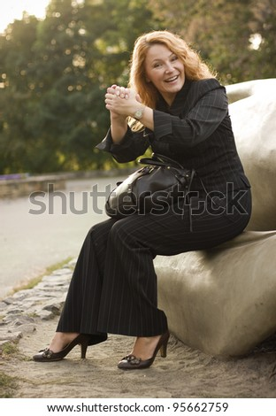 happy business woman resting after successful transaction in the park - stock photo