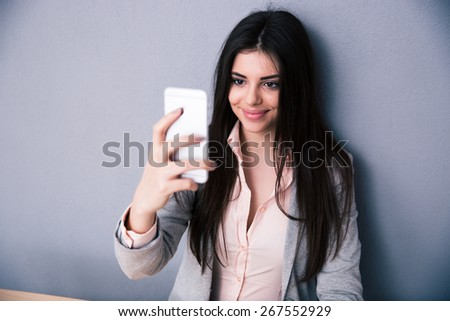 Happy business woman selfie photo on smartphone over gray background - stock photo