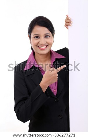 Happy business woman showing blank signboard against white - stock photo