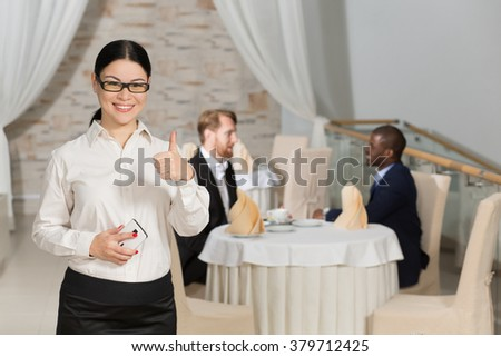Happy business woman showing thumb-up in restaurant while her colleagues or partners communicating on background at table. - stock photo