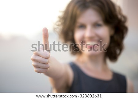 Happy business woman showing thumbs up, standing on the street in summer, friendly smiling, focus on hand - stock photo
