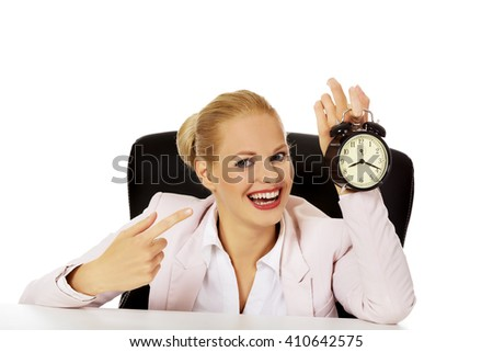 Happy business woman sitting behind the desk and holding alarm clock - stock photo