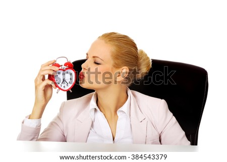 Happy business woman sitting behind the desk and kissing alarm clock - stock photo