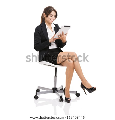 Happy business woman sitting on chair working with a tablet, isolated over white background - stock photo