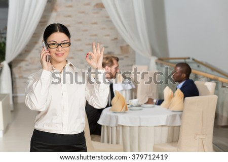 Happy business woman speaking over mobile phone and showing okay while having business meeting in restaurant. - stock photo