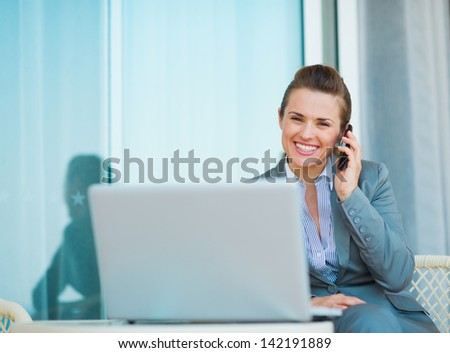 Happy business woman talking mobile phone on terrace