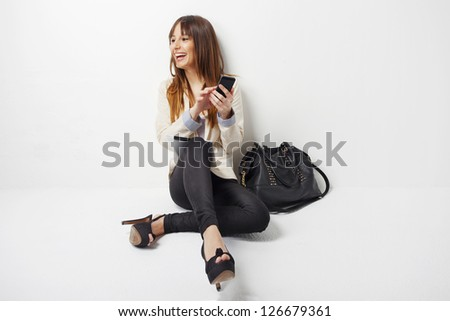 Happy business woman using a smart phone. Young business woman with mobile phone isolated on white