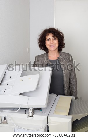Happy business woman using copy machine in office - stock photo