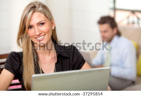 Happy business woman with a laptop smiling - stock photo