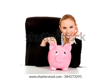 Happy business woman with a piggybank behind the desk