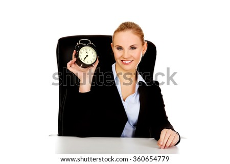 Happy business woman with alarm clock behind the desk - stock photo