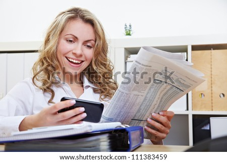Happy business woman with smartphone reading financial section of newspaper in the office - stock photo