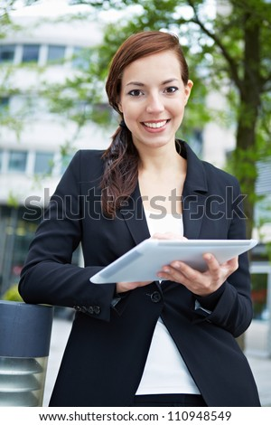 Happy business woman with tablet computer in the city - stock photo