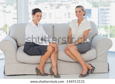 Happy business women sitting on the couch smiling at camera