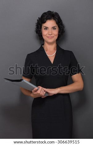 Happy businesslady smiling for the camera over white background. Black-haired woman in business black dress holding documents. - stock photo