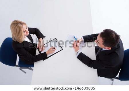 Happy Businessman And Businesswoman Discussing In Office - stock photo