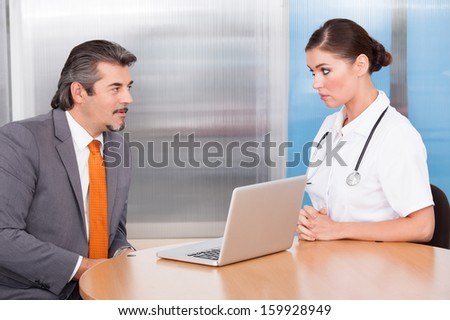 Happy Businessman And Female Doctor Talking Together - stock photo