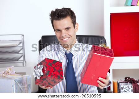 Happy businessman at his office giving christmas gifts