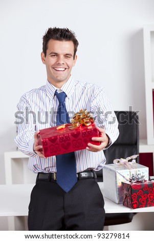Happy businessman at his office giving valentine day gifts - stock photo