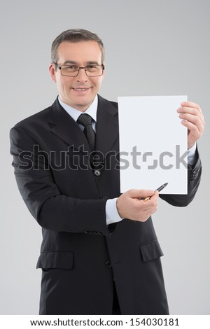 Happy businessman. Cheerful middle-aged businessman holding paper and smiling while standing isolated on grey - stock photo