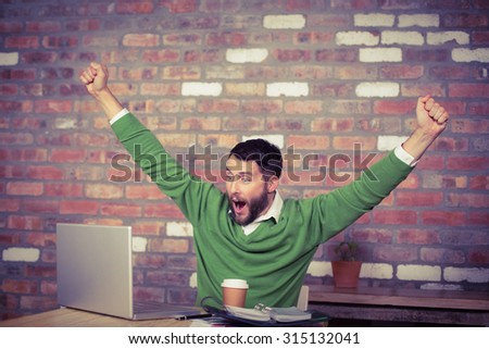 Happy businessman cheering while looking at laptop in office - stock photo