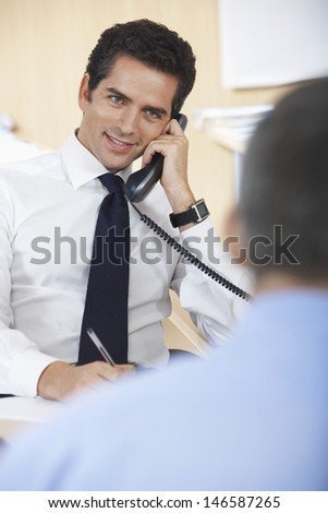 Happy businessman conversing on phone with defocused colleague in foreground