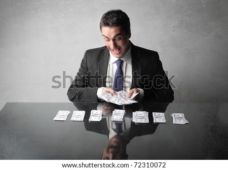 Happy businessman counting out some banknotes - stock photo