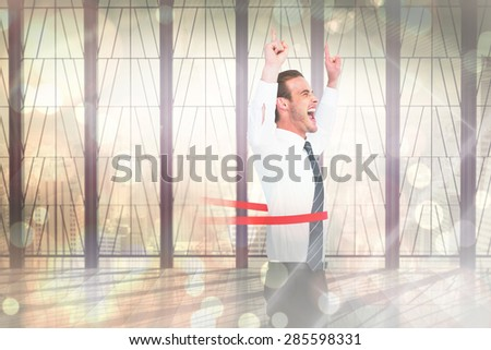 Happy businessman crossing the finish line and pointing up against window overlooking city - stock photo