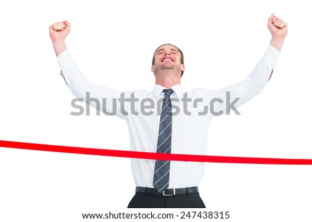 Happy businessman crossing the finish line on white background