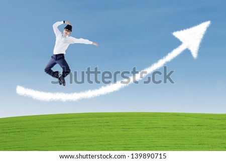 Happy businessman dancing over arrow cloud on the green field - stock photo