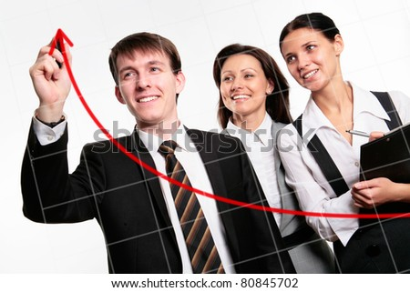 Happy businessman drawing a graph on a glass window in an office - stock photo