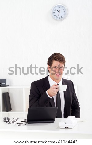 happy businessman drinking coffee in office - stock photo