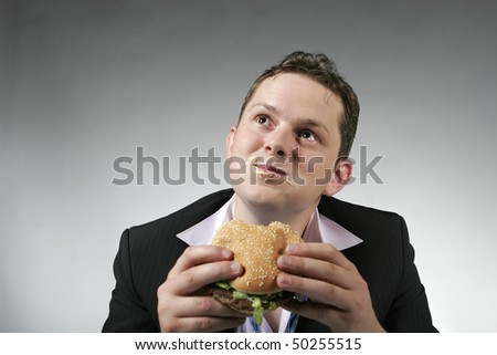 Happy businessman eating junk food. Studio shot - stock photo