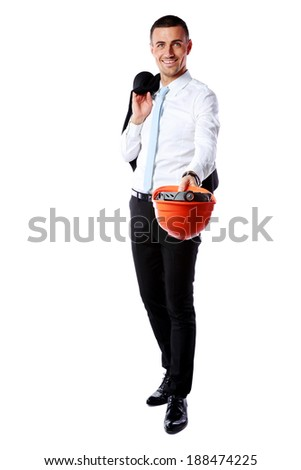 Happy businessman giving helmet at you over white background - stock photo