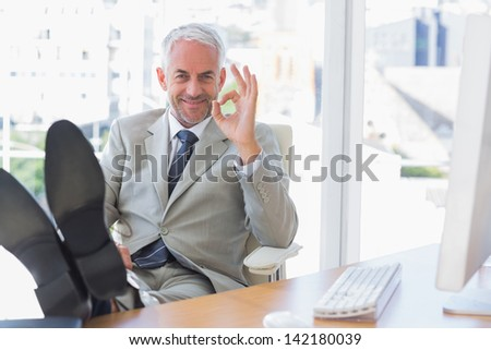 Happy businessman giving ok sign with feet up on his desk - stock photo
