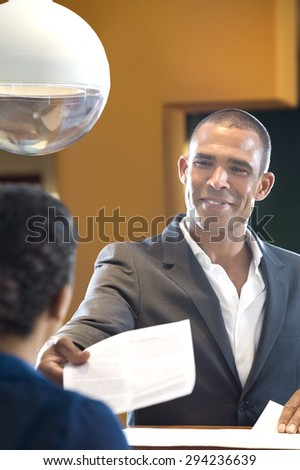 Happy businessman giving paper to receptionist at counter in office - stock photo